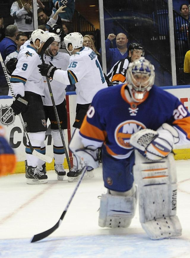 New York Islanders goalie Evgeni Nabokov (20) reacts as San Jose Sharks' Martin Havlat (9), Jason Demers (5) and James Sheppard (15) celebrate Demers' goal in the first period of an NHL hockey game on Friday, March 14, 2014, in Uniondale, N.Y. (AP Photo/Kathy Kmonicek)