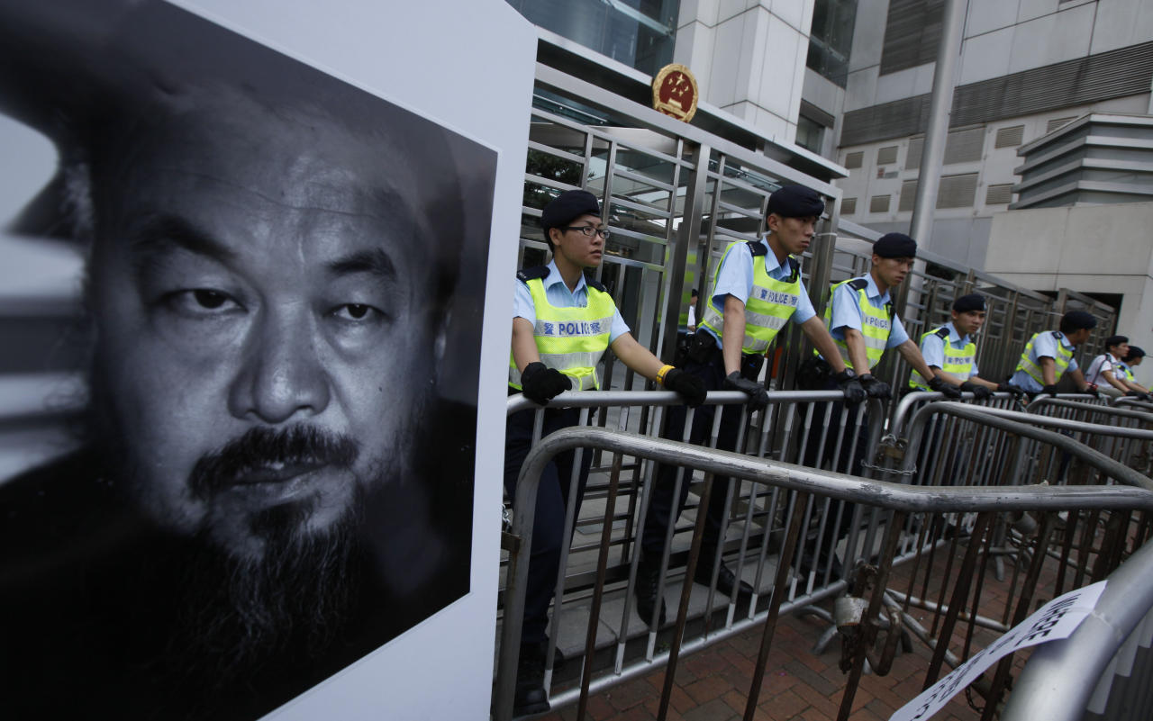 Pro-democracy protesters place a picture of detained Chinese artist Ai Weiwei outside the China Liaison Office in Hong Kong Sunday, April 10, 2011 as they are demanding to release Ai. The sister of the detained Chinese artist says police have still not told the family where he is being held or why, nearly a week after he was grabbed at a Beijing airport.