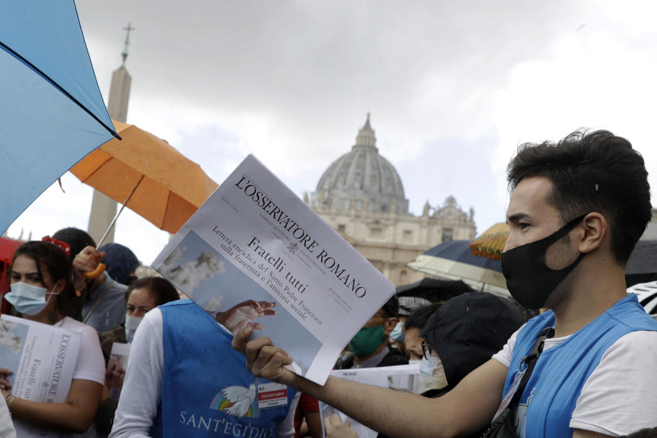 """Free copies of the Vatican newspaper L'Osservatore Romano with the front page about Pope Francis' encyclical """"All Brothers"""" are distributed by volunteers to faithful at the end of the Angelus noon prayer in St. Peter's Square at the Vatican, Sunday, Oct. 4, 2020. Francis on Sunday laid out his vision for a post-COVID world by uniting the core elements of his social teachings into a new encyclical, """"Fratelli Tutti"""" (Brothers All), which was released on the feast day of his namesake, the peace-loving St. Francis of Assisi. (AP Photo/Gregorio Borgia)"""
