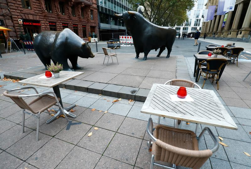 Empty tables are pictured in front of the bull and bear statues outside Frankfurt's stock exchange as the coronavirus disease (COVID-19) outbreak continues in Frankfurt