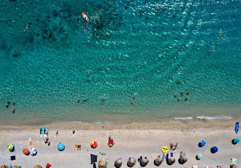 This aerial view taken on August 6, 2019, shows tourists, parasols and buoys on the beach of Llaman, near the city of Himare. - The hot weather conditions of the last days in Albania have seen temperatures reach a peak of 37 degrees Celsius. (Photo by Gent SHKULLAKU / AFP) (Photo credit should read GENT SHKULLAKU/AFP/Getty Images)
