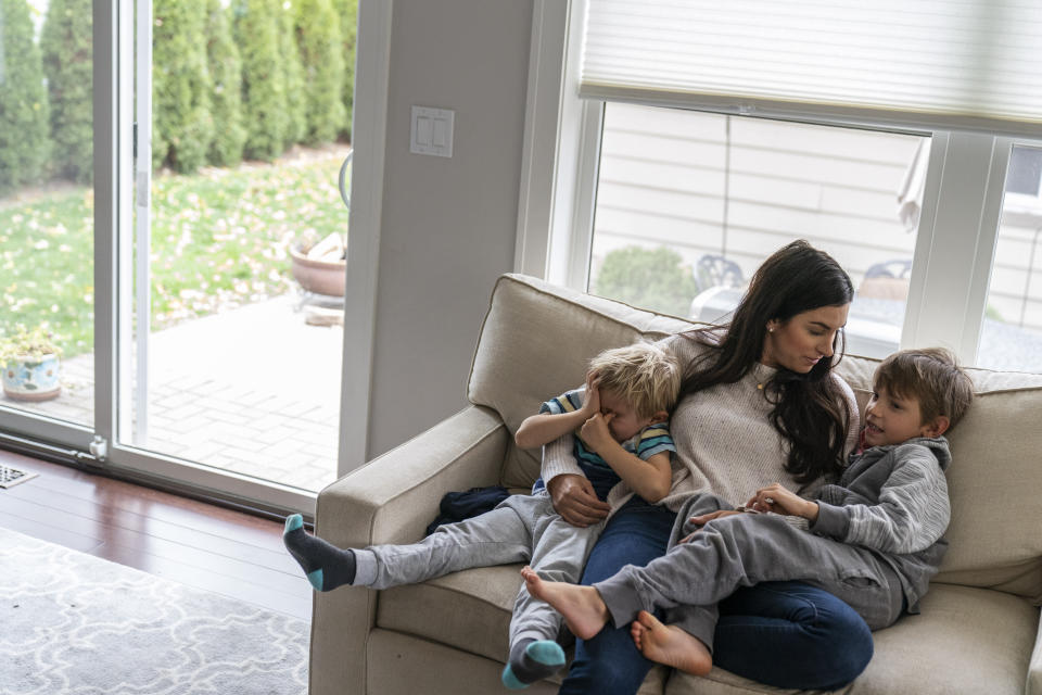 Meghan Iliesiu sits with her sons, Gabriel, 6, right, and Alexander, 4, at their home in Huntington Woods, Mich., Friday, Oct. 30, 2020. Iliesiu, a 32-year-old stay-at-home mother in Oakland County, voted third-party in 2016. She never thought Trump would win. Now she believes he's made the country more hateful and divided. She decided long ago to vote for any Democrat who ran against him. Now the wait is excruciating, Iliesiu said. (AP Photo/David Goldman)