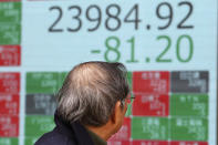 A man looks at an electronic stock board of a securities firm in Tokyo, Wednesday, Dec. 18, 2019. Asian shares were mostly higher Wednesday after record highs on Wall Street amid investor optimism about an interim U.S.-China trade deal announced last week. (AP Photo/Koji Sasahara)