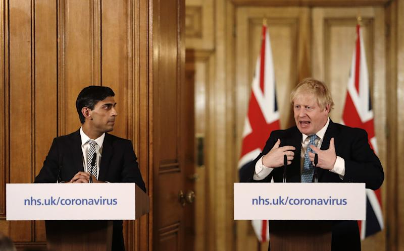 Boris Johnson, U.K. prime minister, right, speaks while Rishi Sunak, U.K. chancellor of the exchequer, listens during a daily coronavirus briefing inside number 10 Downing Street in London, U.K., on Tuesday, March 17, 2020. Photo: Getty
