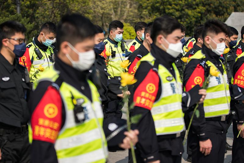 SHANGHAI, CHINA - APRIL 04: Chinese policemen wear protective masks stand in silent tribute during a memorial to mourn for victims of COVID-19 at Shanghai People's Heros Memorial Tower on April 04, 2020 in Shanghai, China. China holds a national mourning on Saturday for martyrs who died in the fight against the novel coronavirus and compatriots died of COVID-19, according to the State Council. During the commemoration, national flags will fly at half-mast across the country as well as in all Chinese embassies and consulates abroad. Public recreational activities will be suspended. At 10:00 am on Saturday, the country will observe three minutes of silence to mourn for the diseased, while air raid sirens and horns of automobiles, trains and ships will wail in grief. (Photo by Yifan Ding/Getty Images)