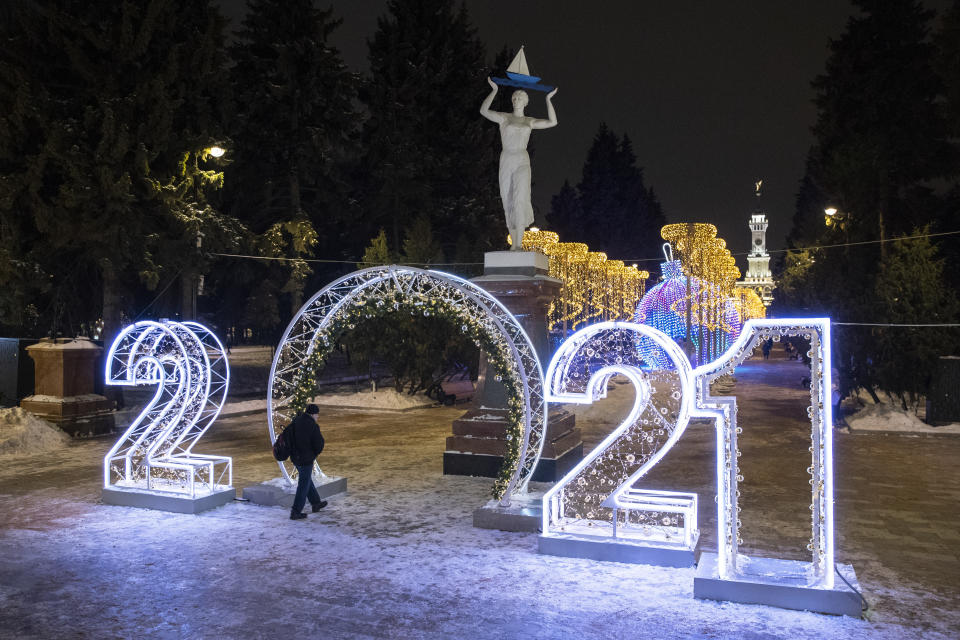 """A man passes """"2021"""" numbers installed to celebrate the upcoming New Year in Moscow, Russia, Tuesday, Dec. 29, 2020. (AP Photo/Pavel Golovkin)"""