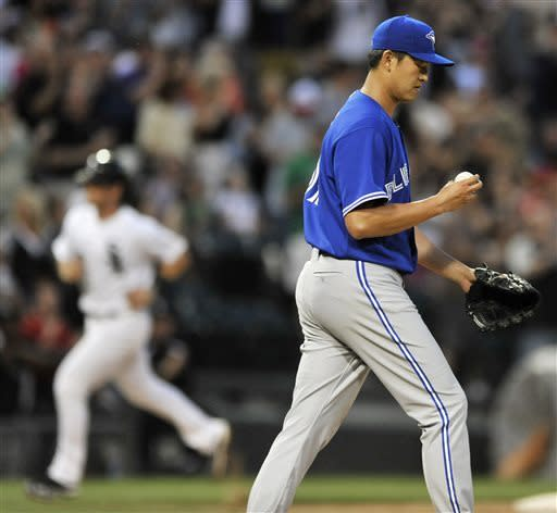 Toronto Blue Jays starting pitcher Chien-Ming Wang reacts as Chicago White Sox's Gordon Beckham rounds third base after hitting a three-run home during the fourth inning of an MLB baseball game in Chicago, Tuesday, June 11, 2013. (AP Photo/Paul Beaty)