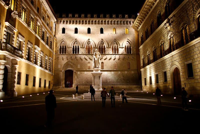 FILE PHOTO: People stroll in front of Monte dei Paschi bank headquarters downtown Siena