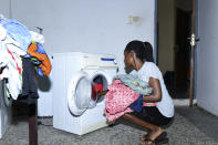 In this photo taken on Wednesday, Oct. 14, 2020, Dodeye Ewa, 16 year does her laundry at her parents house in Calabar, Nigeria. The third child is bothered by President Donald Trump's rhetoric and his policies toward international students, most recently one announced Friday that limits their stays in the U.S. to two or four years with uncertainty about whether their visas will be extended. (AP Photo/Daniel H Williams )