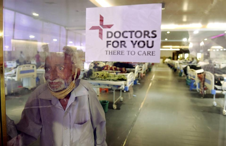 New Delhi: A COVID-19 patient on , Tuesday, 13 April, looks at his family members through a glass barrier at Shehnai Banquet Hall that has been converted into a temporary isolation ward in New Delhi.
