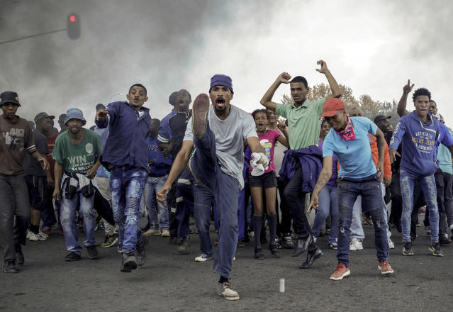 <p>Protesters sing and chant in front of a burning barricade in the Ennerdale, Johannesburg township, May 9, 2017. Violent protests have erupted in South Africa's biggest city for a second day, with police firing rubber bullets at demonstrators who blocked roads and burned tires. (Photo: AP) </p>