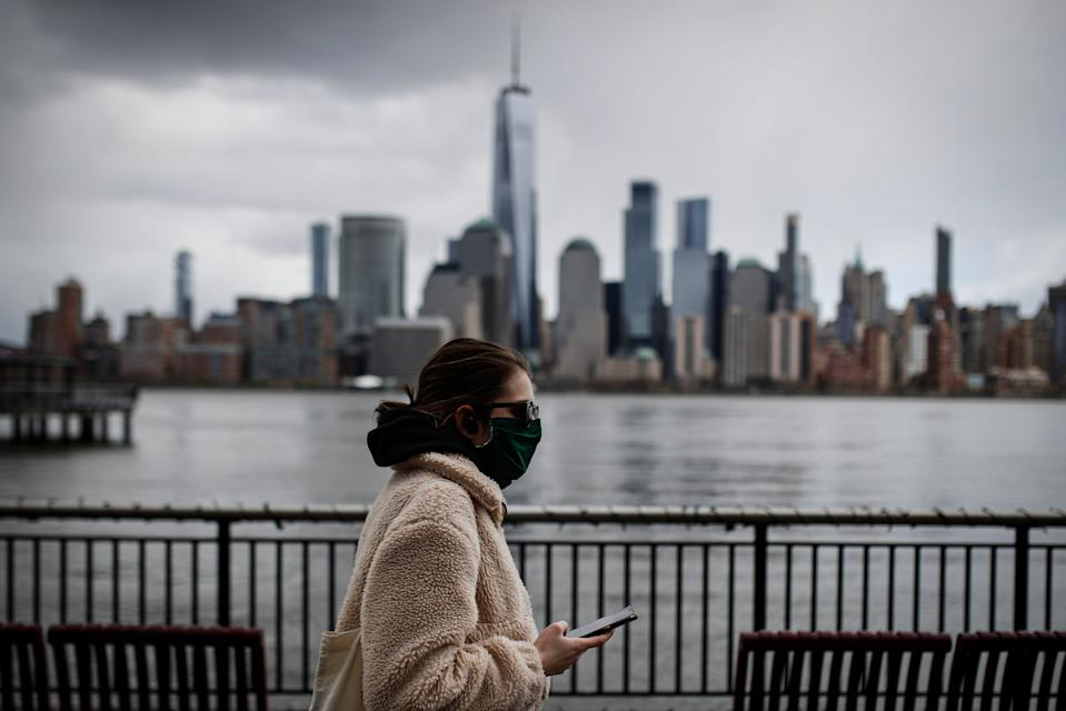 In this April 10, 2020, file photo a woman wearing a face mask sure to COVID-19 concerns walks along the Jersey City waterfront with the New York City skyline in the background.