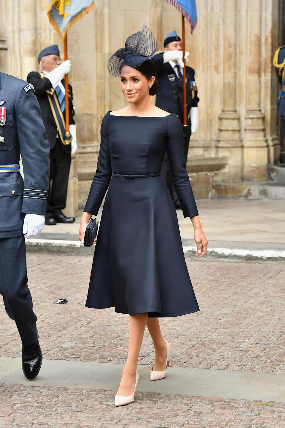 <p>For the RAF's centenary celebrations on July 10, the Duchess of Sussex opted for a bespoke navy-hued dress by Dior. She accessorised the look with a co-ordinating hat by Stephen Jones. [Photo: Getty] </p>