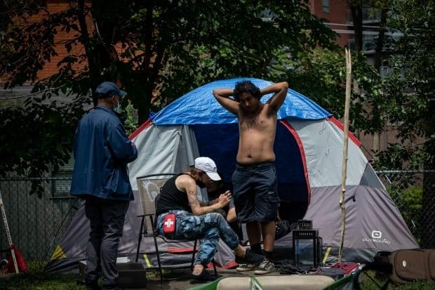 People living in an encampment at Lamport Stadium before they were forcibly evicted by the city and police on July 21, 2021. (Evan Mitsui/CBC - image credit)