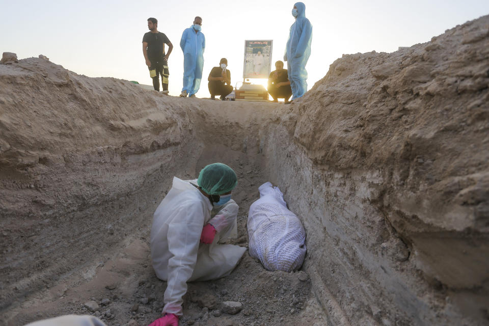 A member of the Shiite Imam Ali brigades militia prays by a body of a coronavirus victim during a funeral at the new Wadi al-Salam cemetery near Najaf, Iraq, Monday, July 20, 2020. A special burial ground near the Wadi al-Salam cemetery has been created specifically for COVID-19 victims since rejections of such burials have continued in Baghdad cemeteries and elsewhere in Iraq. (AP Photo/Anmar Khalil)