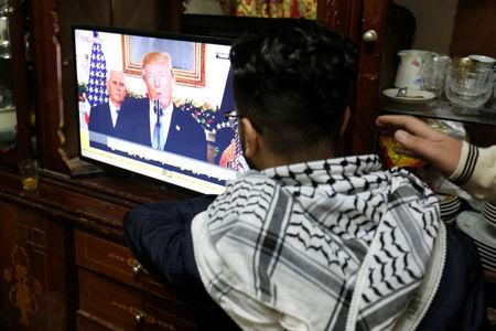 A Palestinian refugee watches a televised broadcast of U.S. President Donald Trump delivering an address where he is expected to announce that the United States recognises Jerusalem as the capital of Israel, at Al-Baqaa Palestinian refugee camp, near Amman, Jordan December 6, 2017. REUTERS/Muhammad Hamed