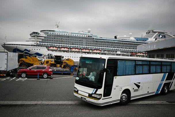 PHOTO: A bus with a driver wearing full protective gear departs from the dockside next to the Diamond Princess cruise ship, which has thousands of people quarantined on board due to fears of the new coronavirus, in Yokohama port, Japan, on Feb. 14, 2020. (Charly Triballeau/AFP via Getty Images)