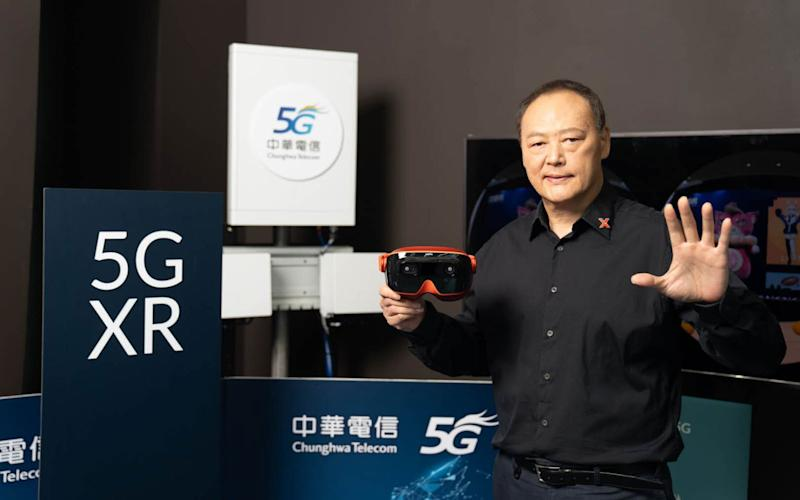 XRSpace CEO Peter Chou showing off his Mova headset in front of Chunghwa Telecom's 5G base station.