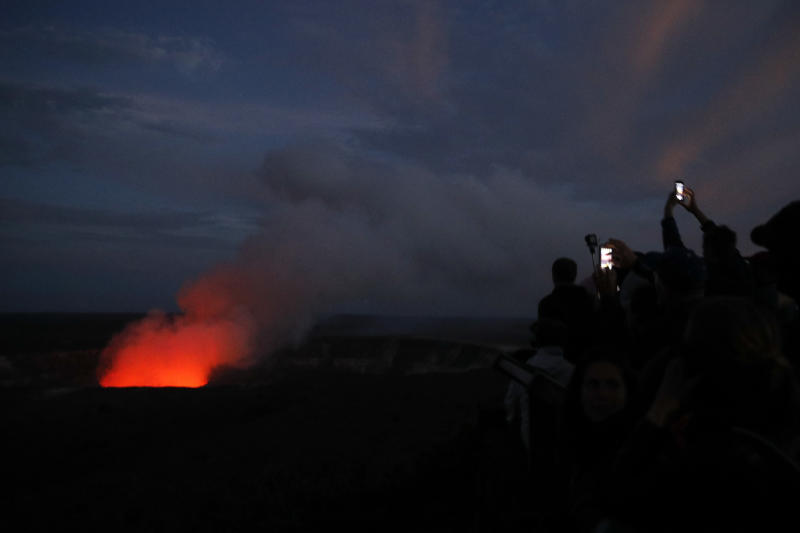 FILE - In this May, 9, 2018, file photo, visitors take pictures as Kilauea's summit crater glows red in Volcanoes National Park, Hawaii. The Hawaii Volcanoes National Park will reopen its main gates Saturday, Sept. 22, 2018, welcoming carloads of visitors eager to see Kilauea's new summit crater and the area where a longstanding lava lake once bubbled near the surface. The park has been closed for 135 days as volcanic activity caused explosive eruptions, earthquakes and the collapse of the famed Halemaumau crater. (AP Photo/Jae C. Hong, File)
