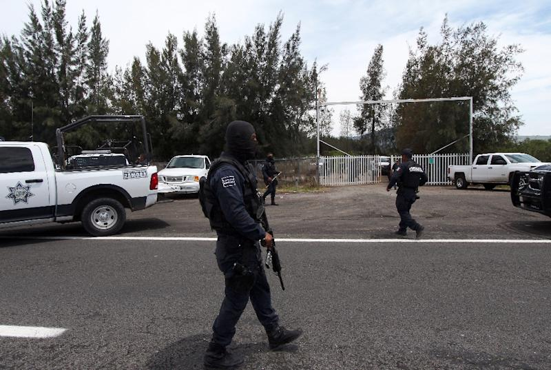 Federal police officers stands guard outside the ranch where gunmen took cover during an intense gun battle with the police, along the Jalisco-Michoacan highway in Vista Hermosa, Michoacan State, on May 22, 2015 (AFP Photo/Hector Guerrero)