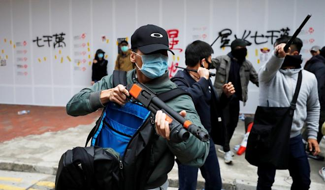 A plain-clothes police officer holds a shotgun to disperse Hong Kong's anti-government protesters on New Year's Day. Photo: Reuters