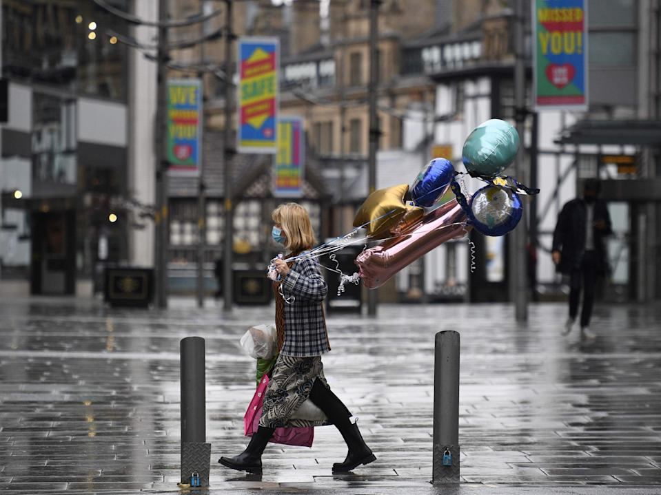 A shopper wears a facemask as she walks along a near-deserted street in Manchester, north west England (AFP via Getty Images)