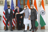 Indian Defence Minister Rajnath Singh, second right, gestures towards U.S. Secretary of State Mike Pompeo, second left, and Secretary of Defence Mark Esper, left, with Indian Foreign Minister Subrahmanyam Jaishankar, right, standing beside him, ahead of their meeting at Hyderabad House in New Delhi, India, Tuesday, Oct. 27, 2020. In talks on Tuesday with their Indian counterparts, Pompeo and Esper are to sign an agreement expanding military satellite information sharing and highlight strategic cooperation between Washington and New Delhi with an eye toward countering China. (Adnan Abidi/Pool via AP)