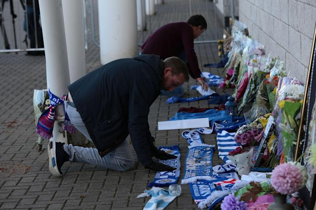 <p>Supporters lay tributes to the Leicester City owner after the crash which killed five people. Aaron Chown/PA Wire </p>