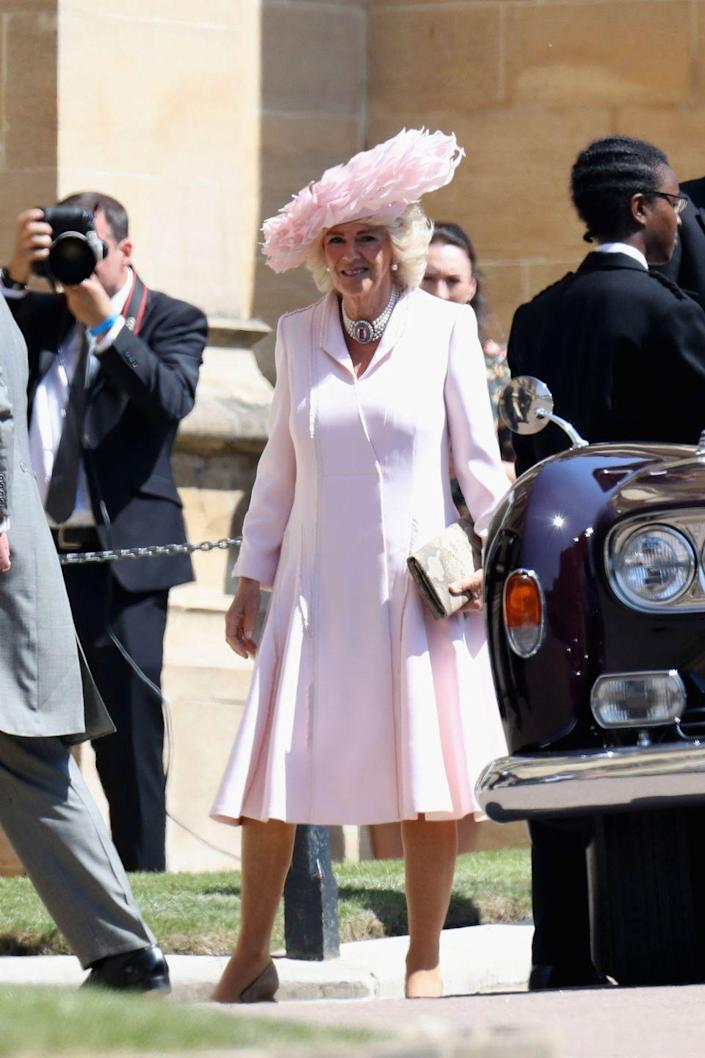 """<p>Camilla stepped out in an ice pink silk coat dress by Anna Valentine and a stunning feathered <a href=""""https://www.townandcountrymag.com/style/fashion-trends/a20631716/camilla-parker-bowles-dress-hat-royal-wedding-2018/"""" rel=""""nofollow noopener"""" target=""""_blank"""" data-ylk=""""slk:Philip Treacy hat"""" class=""""link rapid-noclick-resp"""">Philip Treacy hat</a> at <a href=""""https://www.townandcountrymag.com/society/tradition/g14522381/prince-harry-meghan-markle-royal-wedding-2018-photos/"""" rel=""""nofollow noopener"""" target=""""_blank"""" data-ylk=""""slk:Prince Harry and Meghan Markle's wedding."""" class=""""link rapid-noclick-resp"""">Prince Harry and Meghan Markle's wedding.</a></p>"""