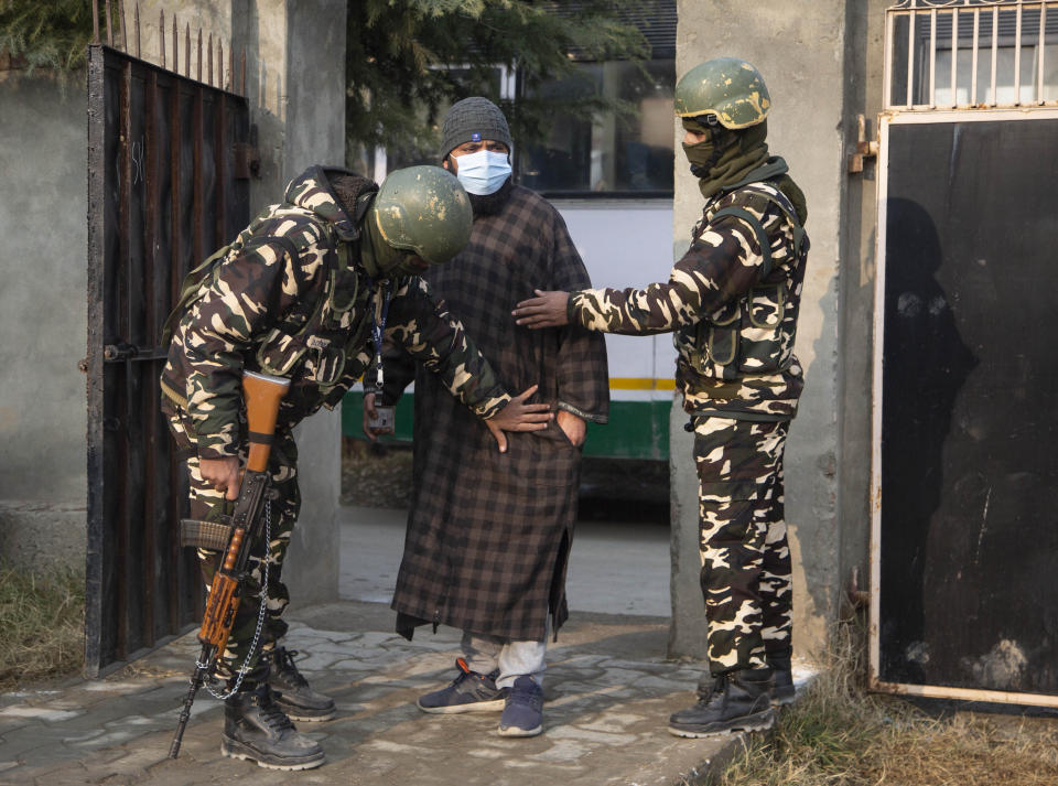 Indian soldiers frisk a voter as he arrives to cast his vote during the first phase of District Development Councils election on the outskirts of Srinagar, Indian controlled Kashmir, Saturday, Nov. 28, 2020. Thousands of people in Indian-controlled Kashmir voted Saturday amid tight security and freezing cold temperatures in the first phase of local elections, the first since New Delhi revoked the disputed region's semiautonomous status. (AP Photo/Mukhtar Khan)