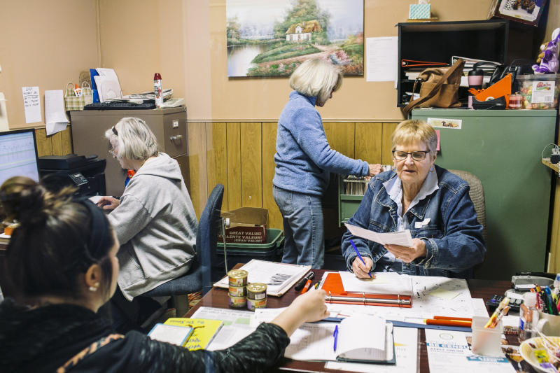 Sherry Perry, right, helps a client at the Eastern Cabell County Humanities Organization food pantry in Milton, W.Va., Jan. 8, 2020. (Andrew Spear/The New York Times)