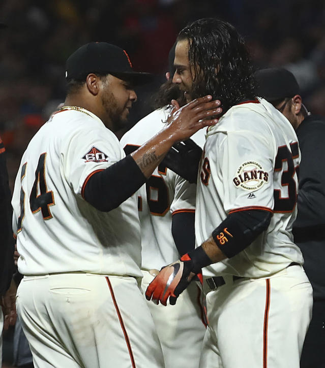 San Francisco Giants' Brandon Crawford, right, celebrates with Reyes Moronta after hitting a walk-off home run off Colorado Rockies Harrison Musgrave during the ninth inning of a baseball game Wednesday, June 27, 2018, in San Francisco. (AP Photo/Ben Margot)