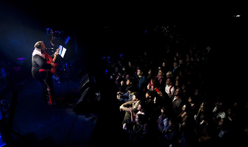 """In this Friday, Sept. 28, 2012 photo, Argentine Elvis Presley impersonator John McInerny performs during a show in Buenos Aires, Argentina. McInerny was chosen to personify the role of Carlos Gutierrez, an Elvis Presley impersonator, in the Argentine film """"The Last Elvis,"""" which premiered last April. McInerny put aside his career as an architect to tour the country performing with his band """"Elvis Lives."""" (AP Photo/Natacha Pisarenko)"""