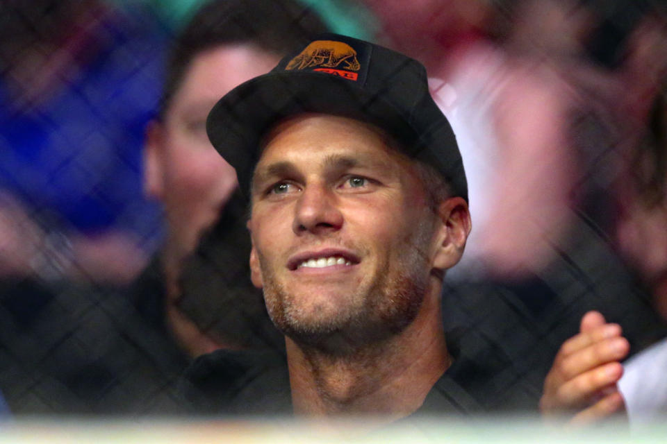 Tampa Bay Buccaneers quarterback Tom Brady watches a UFC 261 mixed martial arts bout, Saturday, April 24, 2021, in Jacksonville, Fla. It is the first UFC event since the onset of the COVID-19 pandemic to feature a full crowd in attendance. (AP Photo/Gary McCullough)