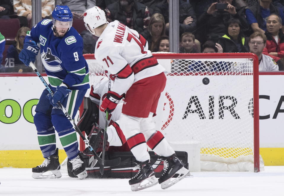 Vancouver Canucks' J.T. Miller (9) and Carolina Hurricanes' Lucas Wallmark (71), of Sweden, watch as the puck goes wide of the goal in front of goalie Petr Mrazek, back, of the Czech Republic, during the first period of an NHL hockey game in Vancouver, British Columbia, Thursday Dec. 12, 2019. (Darryl Dyck/The Canadian Press via AP)