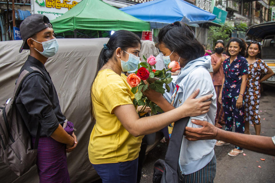 FILE - In this March 26, 2021, file photo, an anti-coup student protester is welcomed home with flowers by the residents of her neighborhood after being released from jail in Yangon, Myanmar. The military takeover of Myanmar early in the morning of Feb. 1 reversed the country's slow climb toward democracy after five decades of army rule. But Myanmar's citizens were not shy about demanding their democracy be restored. (AP Photo, File)