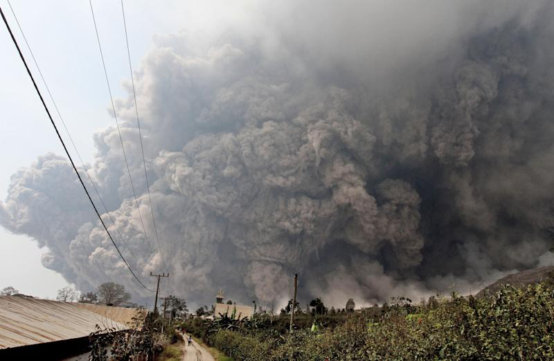 Mount Sinabung releases pyroclastic flows during an eruption as seen from Namantaran, North Sumatra, Indonesia, Saturday, Feb. 1, 2014. The rumbling volcano in western Indonesia has unleashed fresh clouds of searing gas, killing a number people and injuring others. (AP Photo)