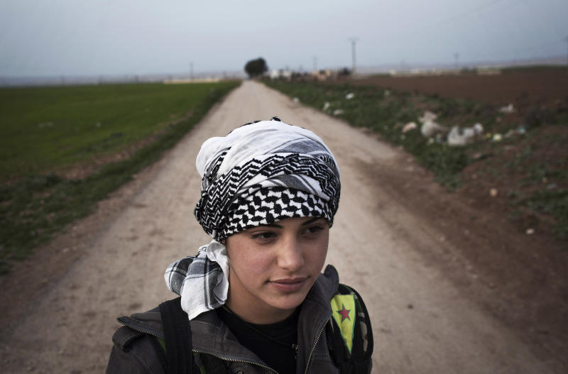 FILE - In this Sunday, March 3, 2013 file photo, A Kurdish female member of the Popular Protection Units stands guard at a check point near the northeastern city of Qamishli, Syria. Taking advantage of the chaos of the civil war, Syria's Kurdish minority has carved out a once unthinkable independence in their areas, creating their own police forces, even their own license plates, and exuberantly going public with their language and culture. (AP Photo/Manu Brabo, File)