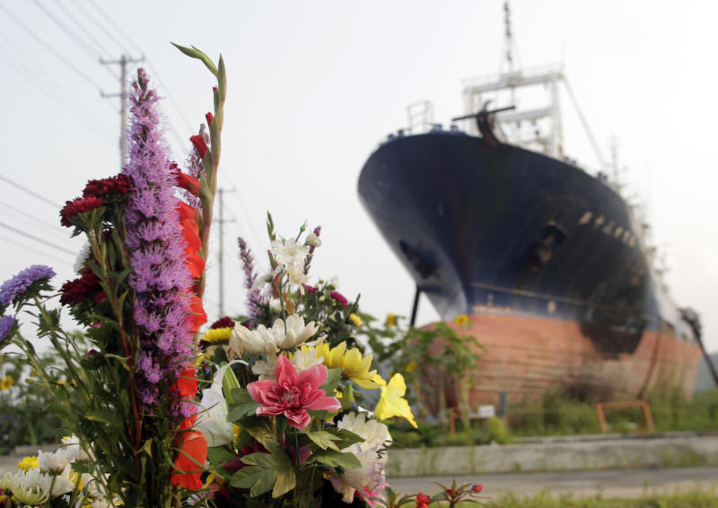 In this photo taken on Sunday Aug. 11, 2013, flowers are left by a stranded fishing boat, which has become a symbol of the devastation of the 2011 tsunami in the northeastern coastal city of Kesennuma. The stranded fishing boat is being torn down. (AP Photo/Azusa Uchikura)