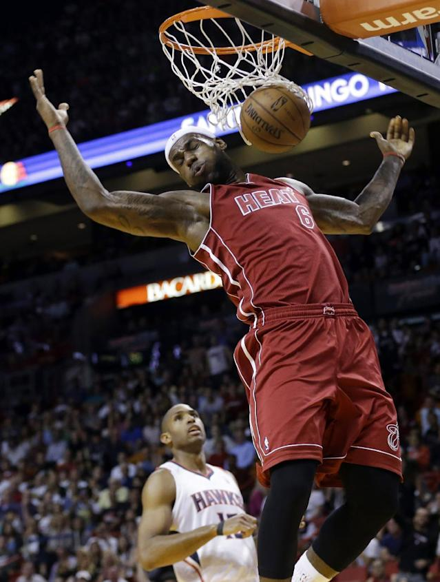 Miami Heat's LeBron James (6) dunks over Atlanta Hawks' Al Horford, left, in the first half of an NBA basketball game, Monday, Dec. 23, 2013, in Miami. (AP Photo/Lynne Sladky)