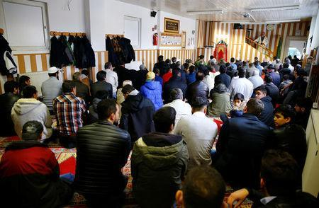Muslims listen to a Turkish imam during Friday prayers at the Turkish Kuba Camii mosque located near a hotel housing refugees in Cologne's district of Kalk, Germany, October 14, 2016. REUTERS/Wolfgang Rattay
