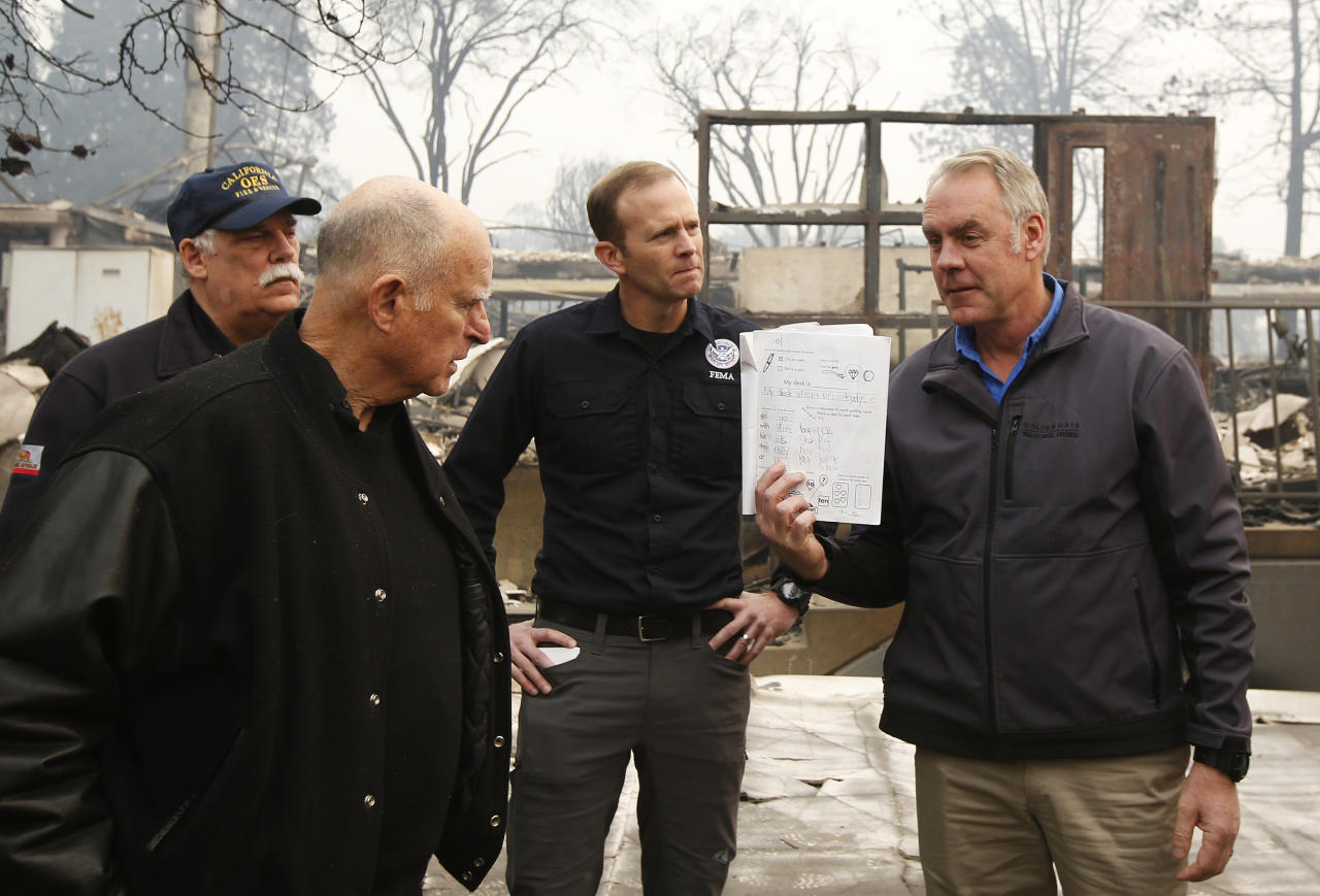 <p>California Gov. Jerry Brown, second from left, looks at a students work book displayed by Interior Secretary Ryan Zinke, that was found during a tour of the fire ravaged Paradise Elementary School Wednesday, Nov. 14, 2018, in Paradise, Calif. (Photo: Rich Pedroncelli/AP) </p>