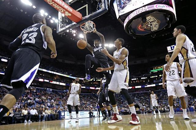 Sacramento Kings center DeMarcus Cousins (15) dunks over New Orleans Pelicans power forward Anthony Davis in the second half of an NBA basketball game in New Orleans, Tuesday, Jan. 21, 2014. The Kings won 114-97. (AP Photo/Gerald Herbert)