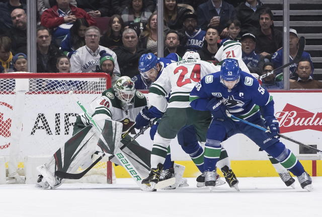 Vancouver Canucks' Tanner Pearson (70) is checked by Minnesota Wild's Matt Dumba (24) in front of goalie Devan Dubnyk (40) during the first period of an NHL hockey game Wednesday, Feb. 19, 2020, in Vancouver, British Columbia. (Darryl Dyck/The Canadian Press via AP)