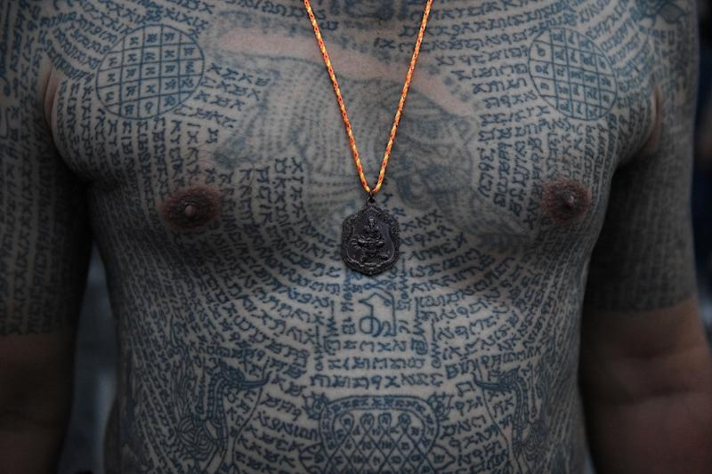 Tattoo wearers believe the intricate ink brings them good luck and protection from harm (AFP Photo/Lillian SUWANRUMPHA)