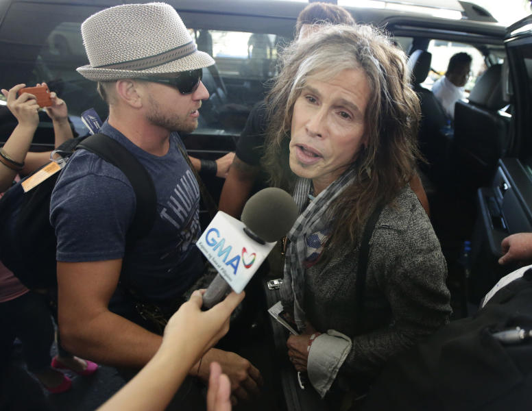 Steven Tyler of the famed Aerosmith rock band is mobbed by reporters as he makes his way to his waiting van upon arrival from Melbourne Sunday May 5, 2013 in Manila, Philippines. Tyler and his entourage are here as part of their band's world tour concert. (AP Photo/Bullit Marquez)