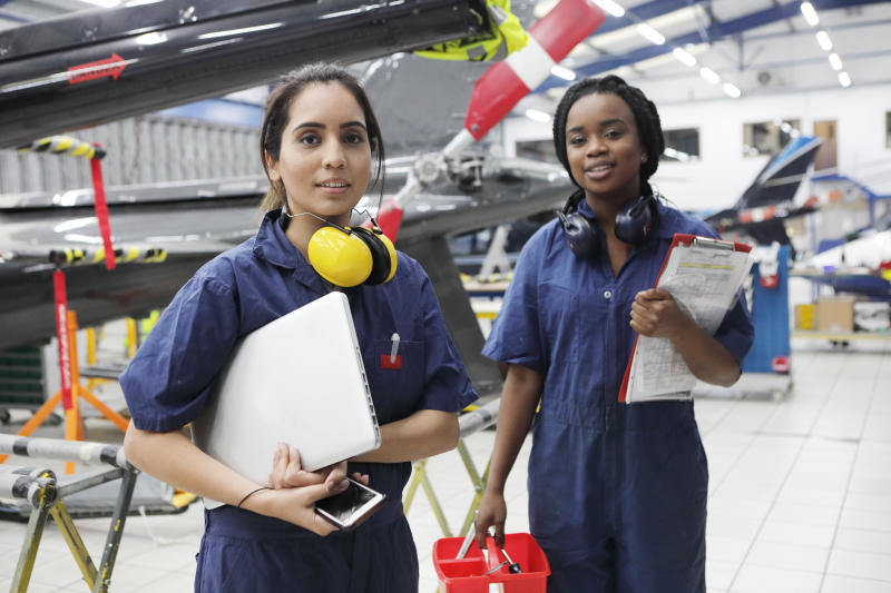 Young female engineers working with helicopters