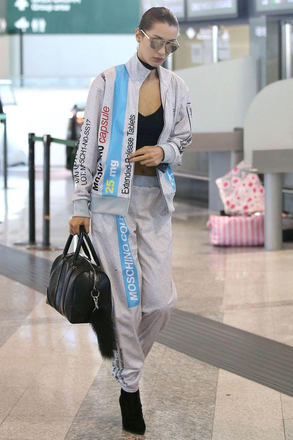 <p>Bella wears a Moschino tracksuit, black heeled boots, a black leather satchel and black top in the Milan airport. </p>
