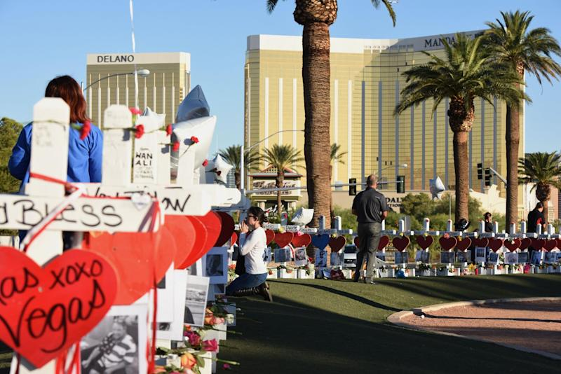 A woman prays beside 58 white crosses for the victims of a mass shooting, on Las Vegas Strip just south of the Mandalay Bay hotel: Getty