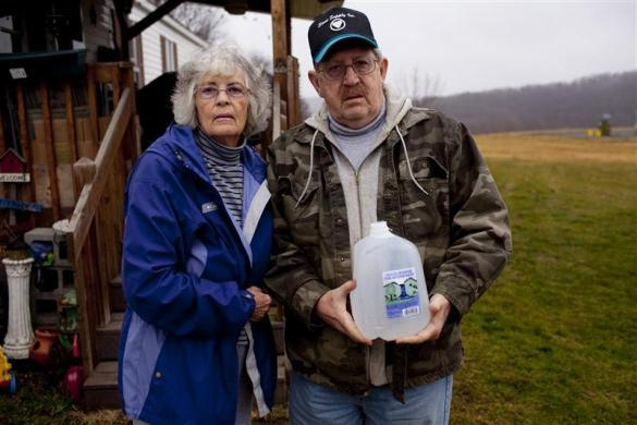 Ron and Jean Carter hold a bottle of their well water outside their home in Dimock, Pennsylvania January 10, 2012.